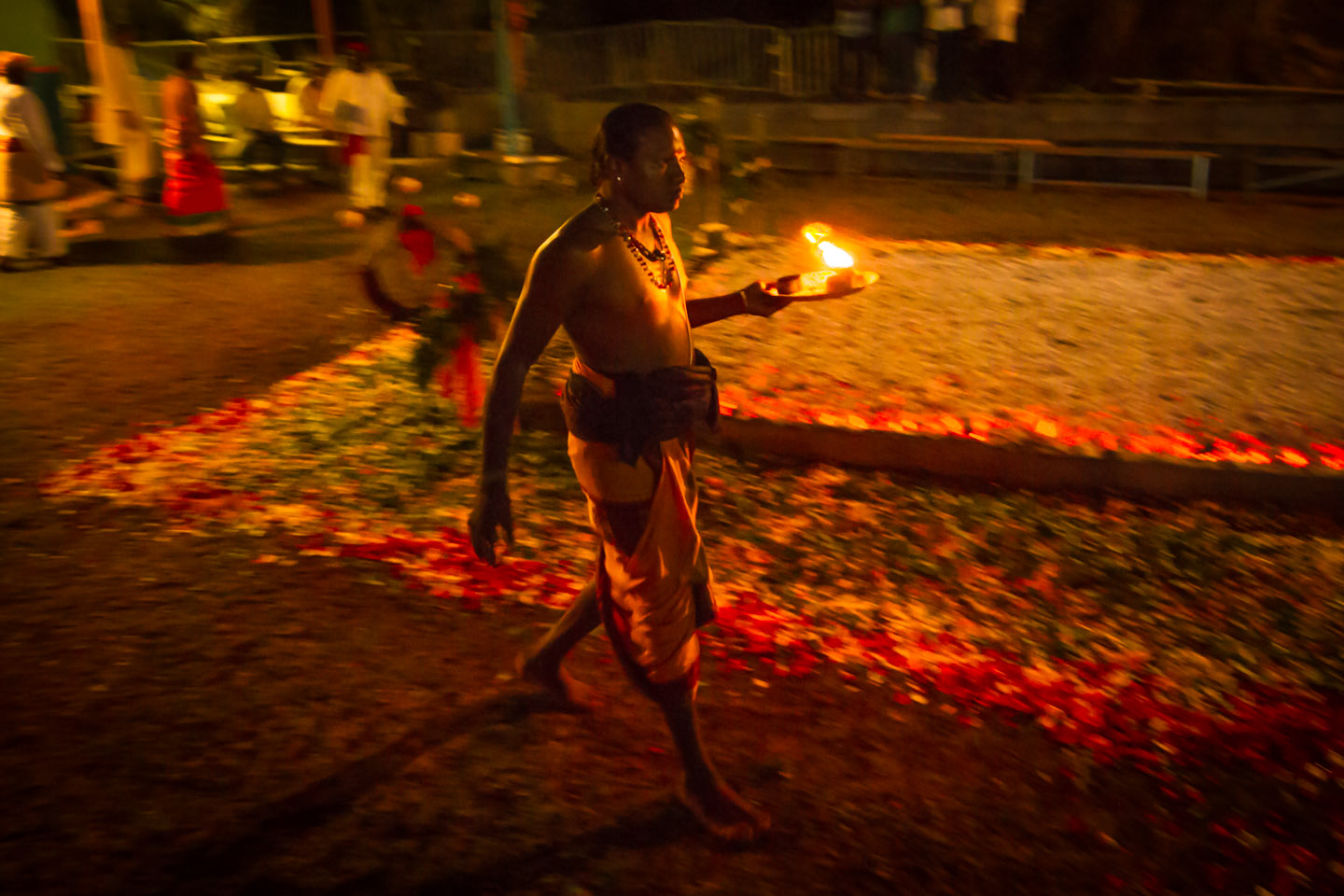 Priest with flowers and fruits offering at Marche sur le feu firewalk La Reunion