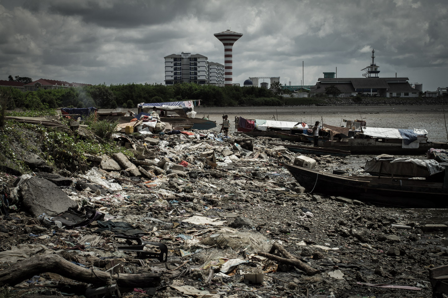 Filipino Philippine illegal immigrants in their boats surrounded by dirt, waste and pollution