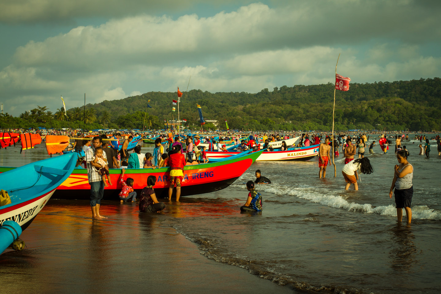 Crowded surfing beach with traditional wooden boats Pangandaran Java boat trip