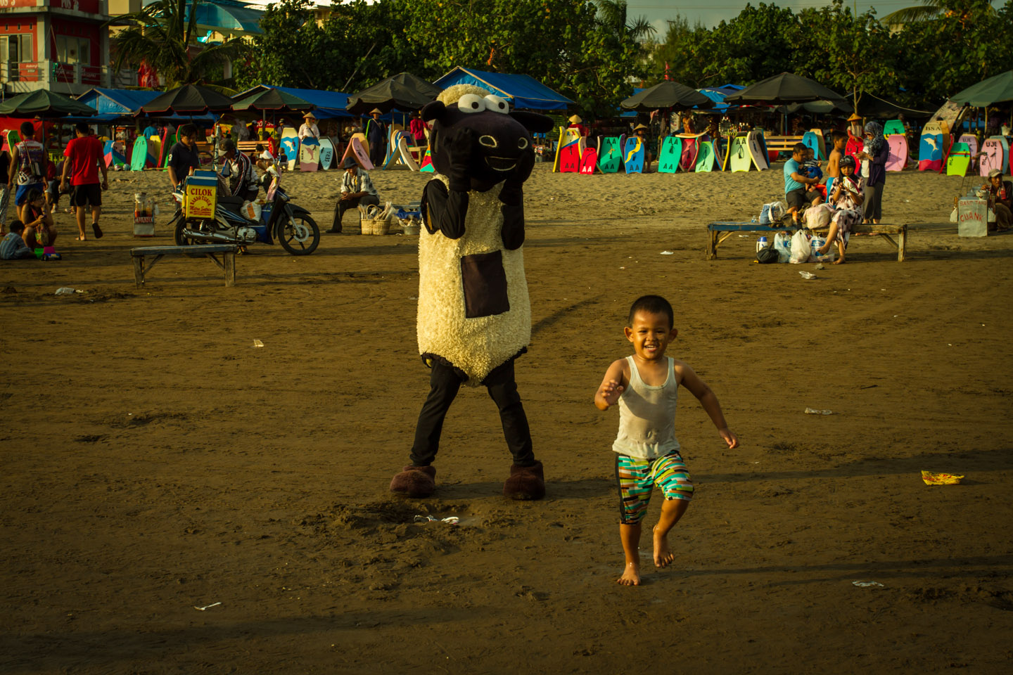 Men dressed as sheep scaring little kid during Ramadan Idul Fitri Pangandaran beach Java Indonesia Indonesien
